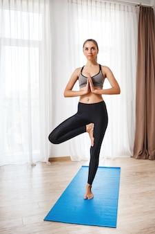 Красивая девушка фитнеса выполняя представление йоги.