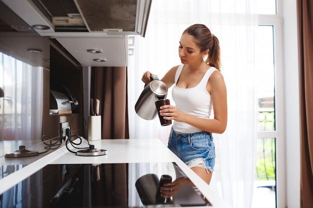 Красивая молодая девушка готовит кофе