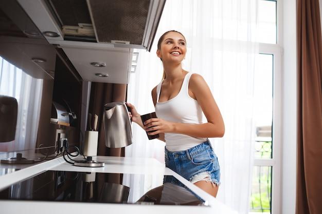 Красивая улыбающаяся молодая девушка делает кофе