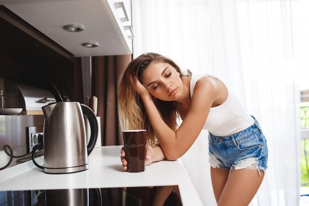 Усталая красивая девушка готовит кофе на кухне