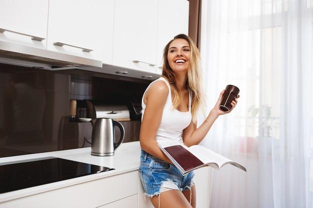 Смеется молодая девушка читает журнал и пьет кофе