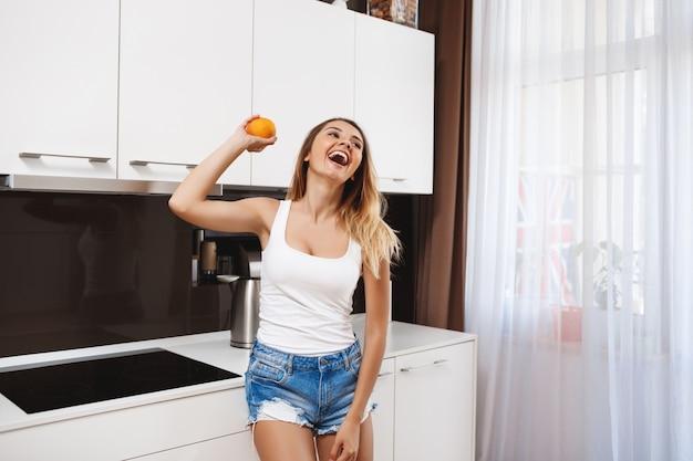 Смеется молодая девушка держит апельсин на кухне