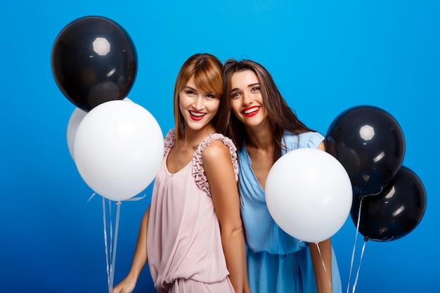 Портрет двух девушек, отдыхающих на вечеринке над синей стеной