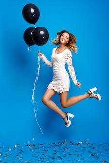 Портрет красивой девушки отдыхает на вечеринке над синей стеной