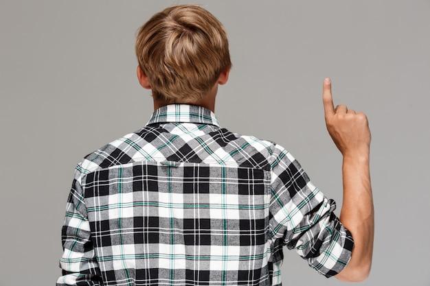 灰色の壁に指で上向き、カメラに戻って立っているカジュアルな格子縞のシャツを着ている金髪の若い男。