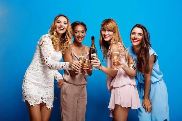 Четыре красивые девушки отдыхают на вечеринке над синей стеной