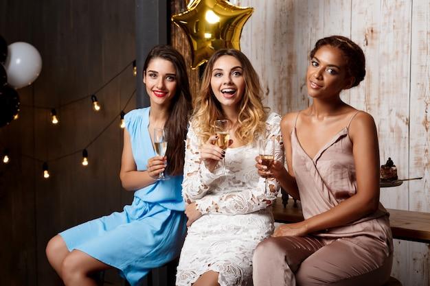 Три красивые девушки отдыхают на вечеринке.