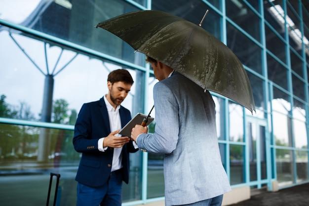 Фотография двух молодых бизнесменов, разговаривающих на дождливой станции