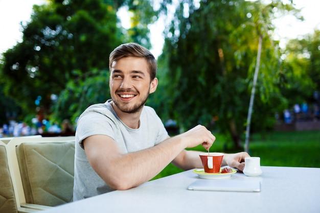 一杯のコーヒーとオープンエアのカフェのテーブルに座っているハンサムな陽気な笑顔若い男。