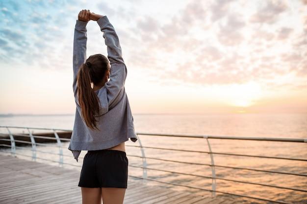 海辺の日の出でトレーニング美しい陽気な少女。
