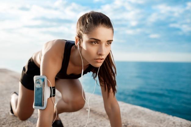Молодая красивая спортивная девушка готовится бежать на побережье.