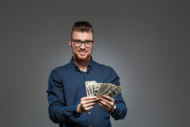 Молодой успешный бизнесмен держа деньги над темной стеной.