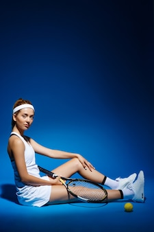 Портрет теннисистки с ракеткой и мячом на полу