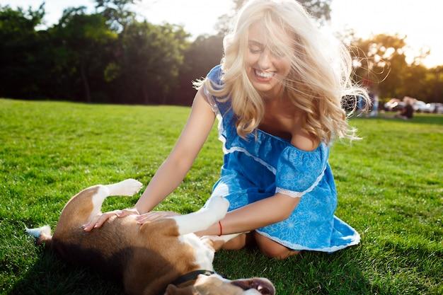 ウォーキング、公園で犬と遊ぶ若い美しいブロンドの女の子。