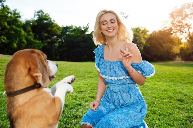 Молодая красивая блондинка девушка прогуливается, играя с бигл собака в парке.