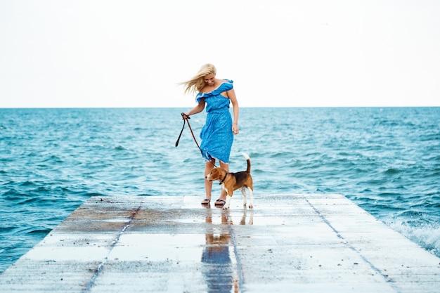 Молодая красивая блондинка гуляя, играя с собакой бигля на взморье.