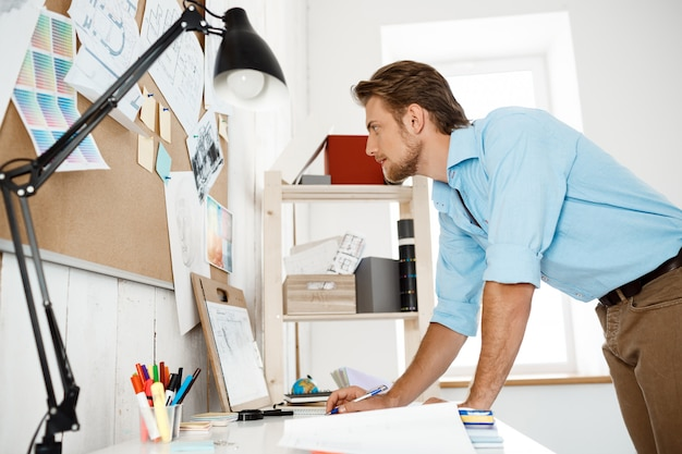 若いハンサムなビジネスマンがテーブルに立って、コルクボードに固定された書類を探して働いています。