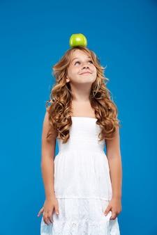 Молодая милая девушка держа яблоко на голове над голубой стеной