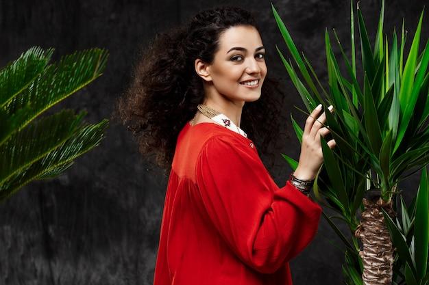 Молодая красивая брюнетка девушка в тропических растениях на серую стену