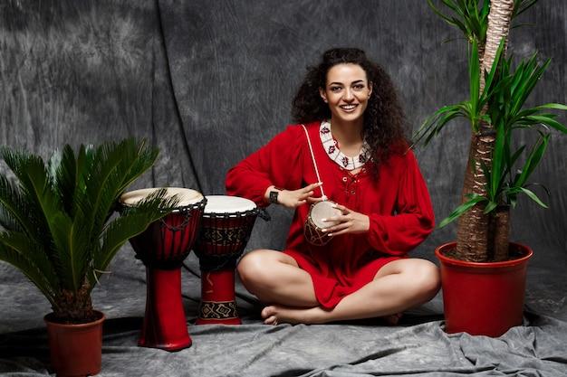 Красивая девушка играет барабан в тропических растений на серую стену