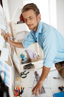若いハンサムなビジネスマンがテーブルに立って、紙に書いてコルクボードに固定されています。
