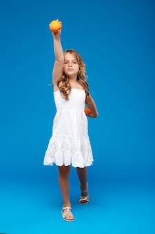 Молодая милая девушка держа апельсины над голубой стеной
