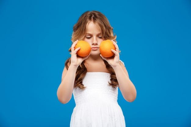 青い壁にオレンジを置く若いきれいな女の子