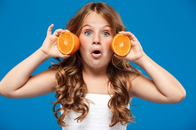 水色の壁にオレンジを置く驚いた若いきれいな女の子