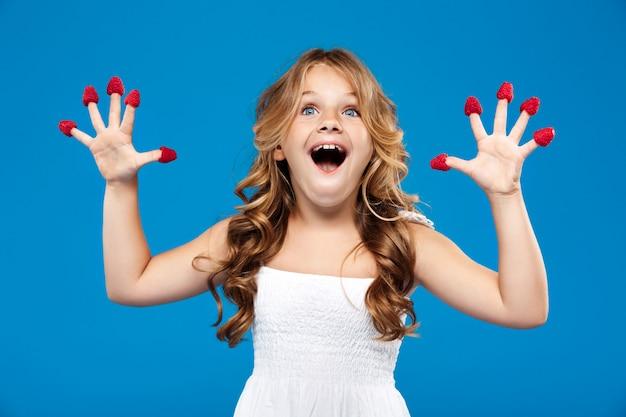 青い壁にラズベリーを保持している驚きの若いかわいい女の子
