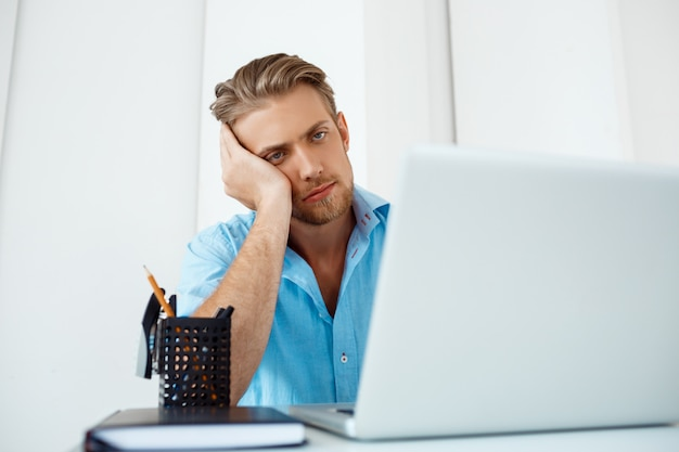 若いハンサムな疲れて自信を持って物思いにふけるビジネスマンは、一杯のコーヒーを脇にラップトップに取り組んでいるテーブルに座っています。白い近代的なオフィスインテリア