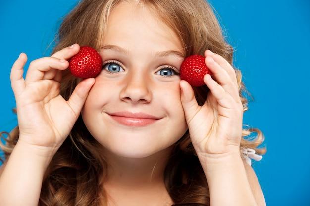 青い壁にイチゴを置く若いきれいな女の子