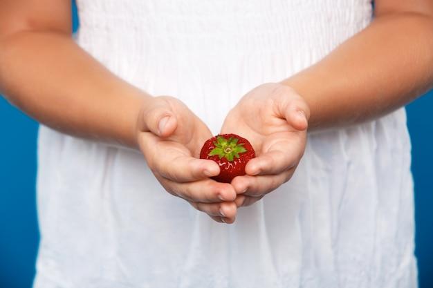青い壁にイチゴを持っている女の子の手のクローズアップ