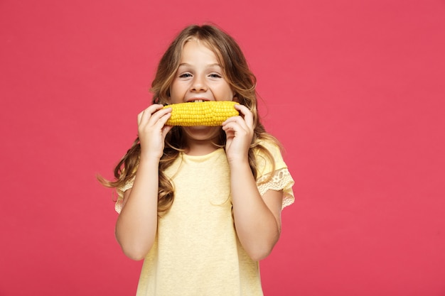 Молодая красивая девушка ест кукурузу над розовой стеной