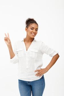 Портрет молодой красивой африканской девушки над белой стеной