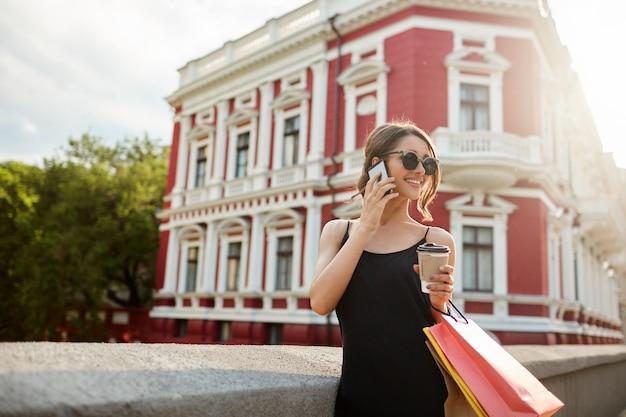 通りを歩いてきれいな女性。笑って、赤い建物の近くを歩いて、陽気な表情をよそ見、バッグを手で押し、笑って成功した後幸せな若い魅力的な女性の女の子
