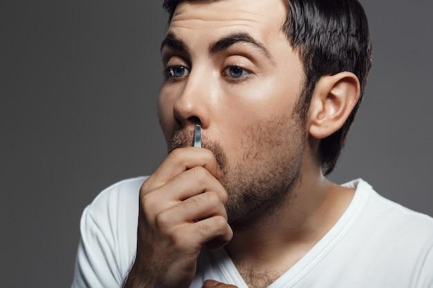 灰色の壁を越えて鼻で髪をピンセット若いハンサムな男