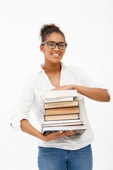 Портрет молодой африканской девушки с книгами на белой стене