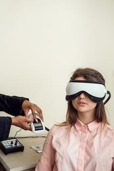 Горизонтальный портрет милой европейской пациентки, сидящей в кабинете окуляра, носящей устройство для проверки цифрового зрения во время тестирования зрения, ожидающего окулисту, чтобы закончить проверку