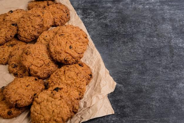 Сладкое овсяное печенье на бумагу для выпечки на деревянный стол