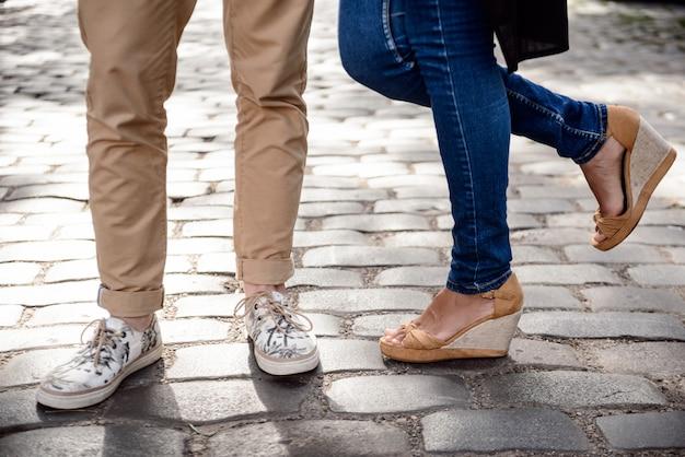通りに立っているケッズでカップルの足のクローズアップ。
