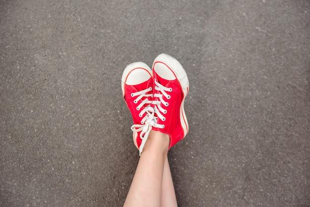 アスファルトの上に横たわる赤いケッズの足のクローズアップ。