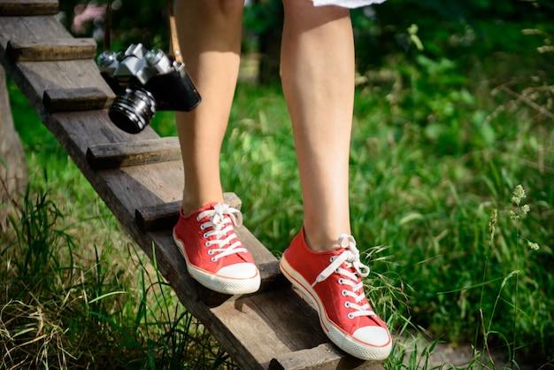 机を踏んで赤いケッズの足のクローズアップ。