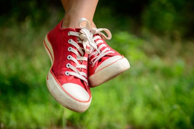 草の上の赤いケッズで女の子の足のクローズアップ。