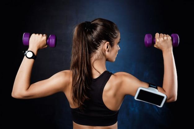 Молодая красивая спортивная девушка тренировки с гантелями над темной стеной.