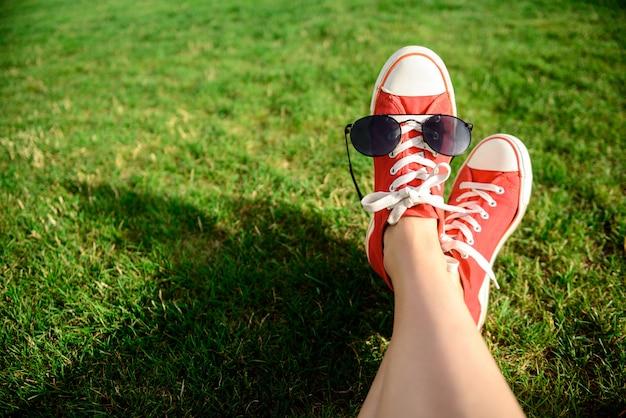 草の上に横たわる赤いケッズの足のクローズアップ。