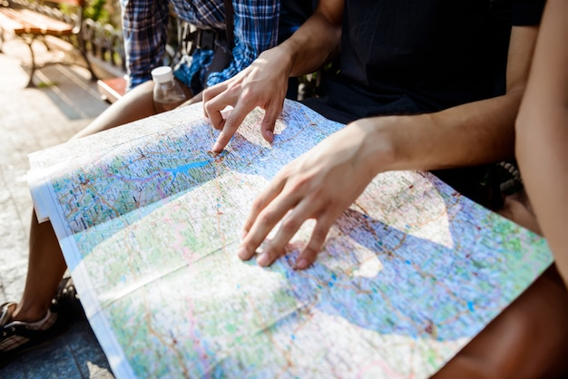 Друзья путешественников улыбаются, смотрят маршрут на карту, сидят на скамейке.