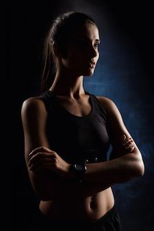 暗い壁を越えて組んだ腕でポーズ美しいスポーツ少女。
