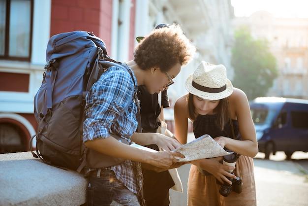 Друзья путешественников с рюкзаками улыбаются, смотрят маршрут на карту на улице.