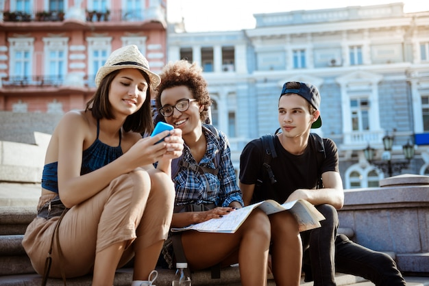 笑顔、携帯電話を見て、近くに座ってバックパックと友達。