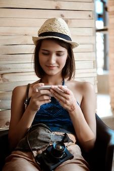 Молодая красивая брюнетка женщина фотограф, глядя на телефон, улыбаясь.